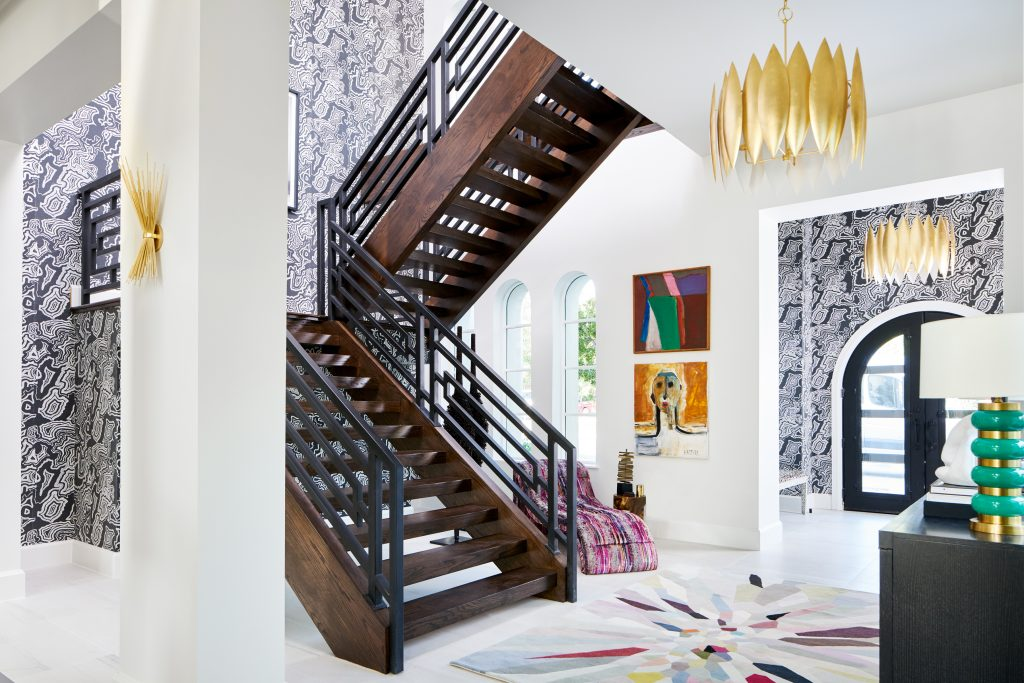Traditional Home Dallas Showhouse, Bridget Beari Wallcovering, Buscemi wall covering, tina turner art, geometric railing, chaise lounger, s. harris brushstroke, double volume entry, modern staircase, entryway, circa lighting, gold chandelier, green and gold lamp, easel, Jonathan Adler easel, coffee table books, tom ford book, harpers bazaar book, credenza, dark credenza, black credenza, circle accent furniture, bowl, s. harris, drapery, curtains , gold lighting, gold chandelier, colorful rug, the rug company, original art, human form art