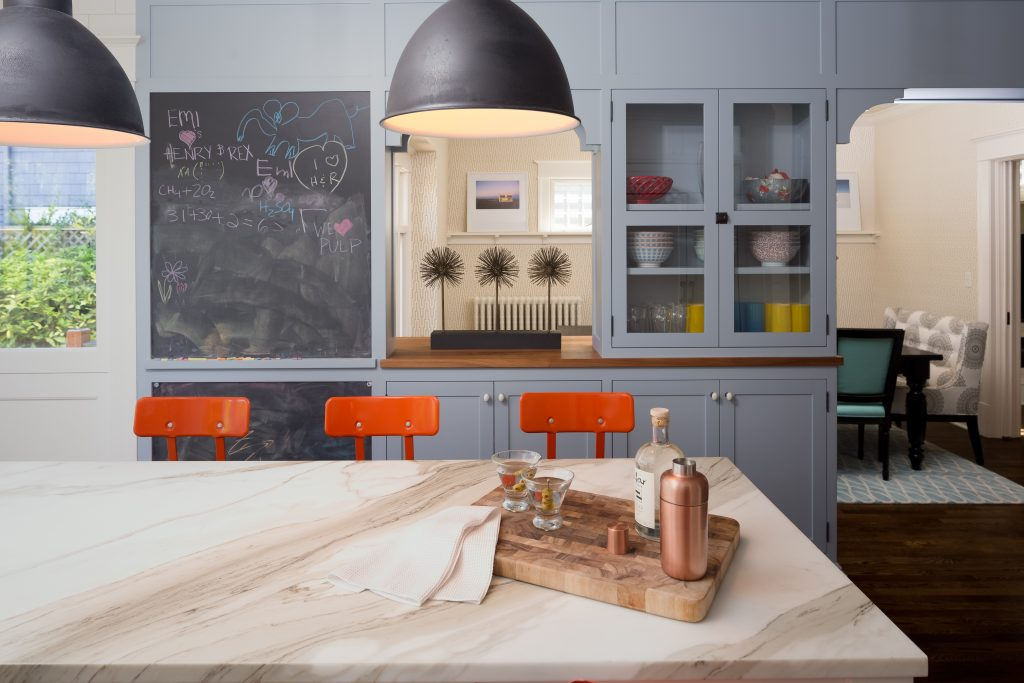 Fearless Style Fit for a Family, Kitchen featuring colorful orange bar stools, black pendant lighting, chalk board paint, chalk board wall, blue kitchen cabinets, painted kitchen cabinets, modern coastal style family home