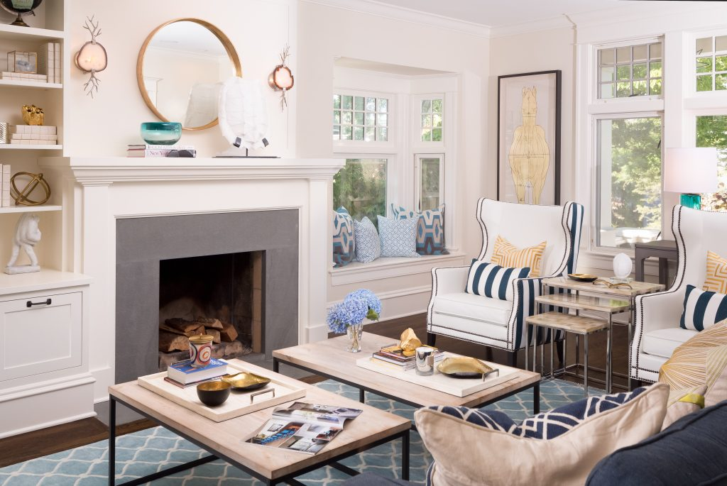 Fearless Style Fit for a Family, Living Room featuring navy blue stripped armchairs, geometric blue rug, circle mirror, gold accented artwork, horse inspired artwork, coastal style family home