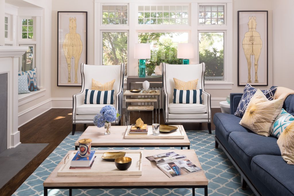 Fearless Style Fit for a Family, Living Room featuring navy blue stripped armchairs, geometric blue rug, circle mirror, gold accented artwork, horse inspired artwork, coastal style family home, coffee table styling
