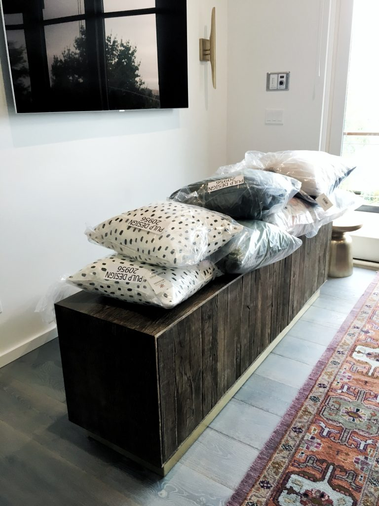 Wood credenza and accent pillow interior design installation