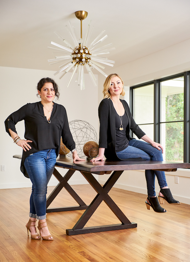 Two luxury interior designers sitting on a dining table with brass starburst chandelier at Pulp Design Studios