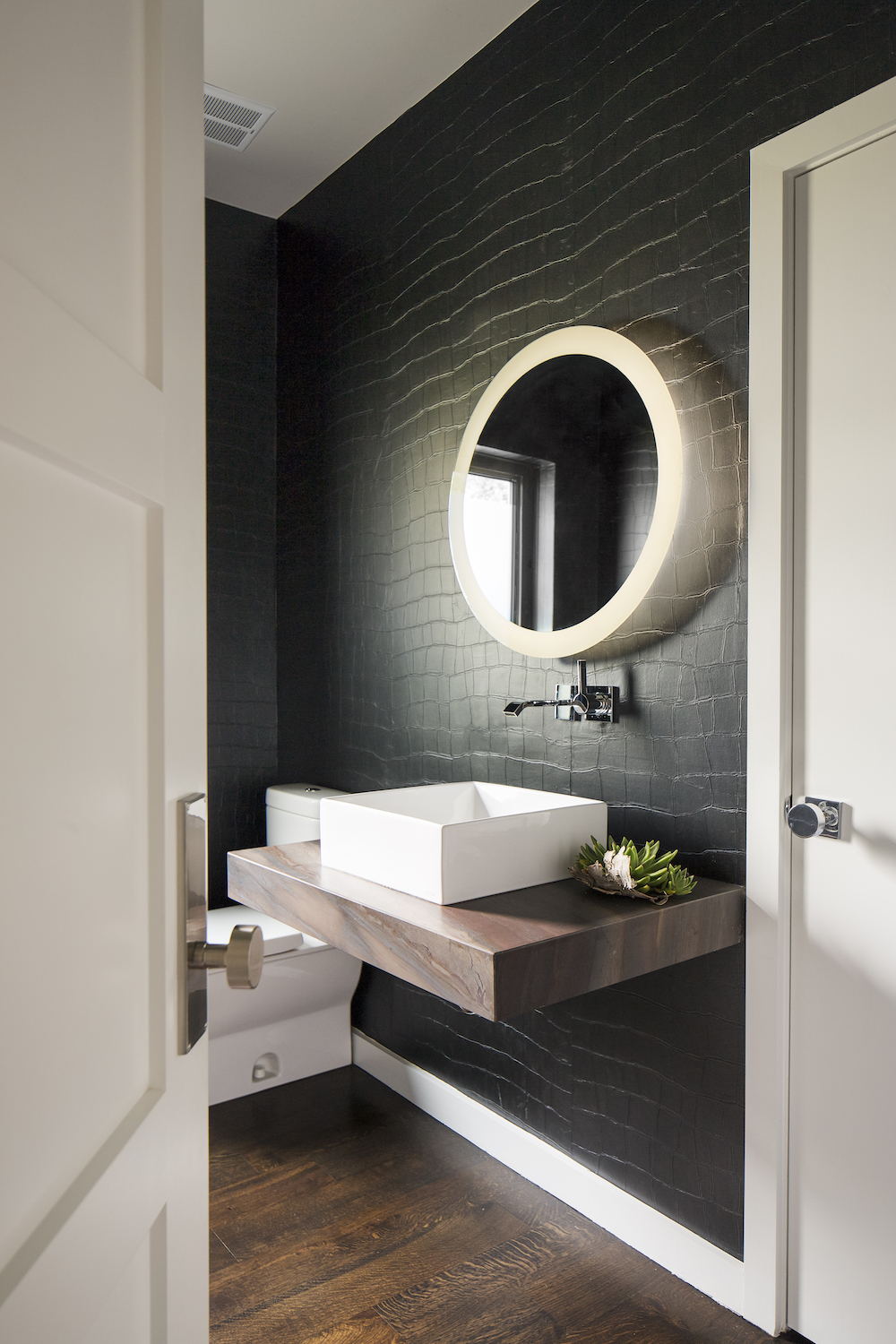 Contemporary powder bathroom interior design with circular mirror, crocodile inspired dark wallcovering and modern fixtures.